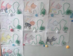 Prace plastyczne wiszące na tablicy, przedstawiające koty z włóczką