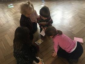 Dzieci siedzące na podłodze, oglądające kolorowe obrazki