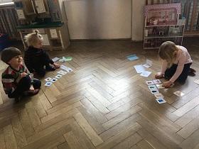 Dzieci siedzące na podłodze na przeciwko siebie, układające przed sobą kartoniki z kolorowymi obrazkami
