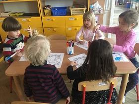 Dzieci pracujące przy stole, kolorujące flamastrami prace