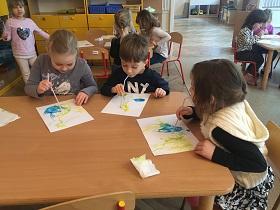 Dzieci siedzące przy stoliku, trzymające w buzi słomki i dmuchające w nie, na kartkę papieru, na której znajduję się farba.