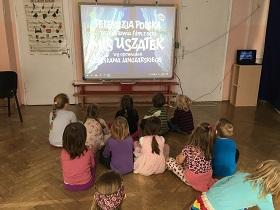 Dzieci siedzące na podłodze w sali, wpatrujące się w tablicę interaktywną. Na tablicy napis: Telewizja Polska przedstawia film z serii Miś Uszatek wg. Opowiadań Wiesława Janczarskiego.