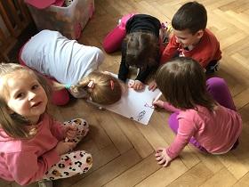 Dzieci siedzące na podłodze i rysujące flamastrami na kartce rozmiaru A3.