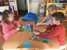 Dzieci siedzące przy stoliku. Na stole leżą maty, na których dzieci lepią coś z żółtej plasteliny.