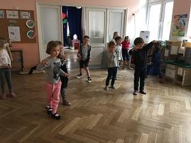 Dzieci stojące na podłodze w sali, wskazujące przed siebie ręką oraz stojące w bezruchu.