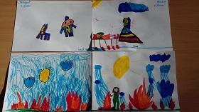 Prace plastyczne dzieci narysowane flamastrami, leżące na stole. Przedstawiające strażaka, lekarza oraz policjanta.