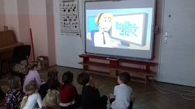 Dzieci siedzące na podłodze w siadzie skrzyżnym, wpatrujące się w tablicę interaktywną. Na tablicy – pani trzymająca przy uchu słuchawkę i patrząca na monitor komputera.
