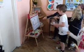Dzieci trzymające skakankę w rękach, stojące w większej grupie. Trzymające skakankę w kierunku tablicy, na której jest napis: Kazimierzowska.