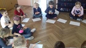 Dzieci siedzące w kółku, w siadzie skrzyżnym. Przed nimi leży biała kartka A4. Dzieci trzymają w rękach kredki.
