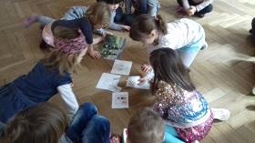 Dzieci siedzą na podłodze w sali i oglądają ilustracje, które leżą na środku sali.