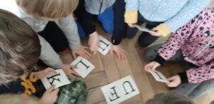 Na podłodze siedzą dzieci, każde ma w ręku kartonik z literą. Na podłodze leżą dwie litery UF.