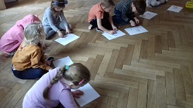 Dzieci siedzą na podłodze w sali. Przed nimi leżą białe kartki A4, na których ułożone są kolorowe patyczki. Dzieci patrzą na kartki.
