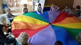Dzieci siedzą i trzymają kolorową chustę animacyjną w dłoniach. Mają schowane nogi pod chustą