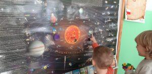 Przed mapą układu słonecznego stoją dwaj chłopcy, chłopiec z lewej strony wskazuje Ziemię.