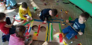Na podłodze wokół dużego kształtu rakiety siedzi pięcioro dzieci, wyklejają ją paskami kolorowej krepiny.