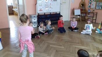 Dzieci siedzące w kółku w siadzie skrzyżnym. Trzymające w rękach instrumenty muzyczne. Jedno dziecko stoi tyłem i trzyma w ręku drewnianą pałkę.