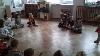 Dzieci siedzące w kółku w siadzie skrzyżnym. Trzymające w rękach instrumenty muzyczne. Jedno dziecko stoi i trzyma w ręku drewnianą pałkę.