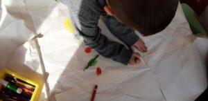 Na dużym kartonie papieru chłopiec rysuje planety z układu słonecznego