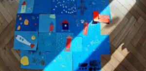 Na niebieskich kartkach przyklejone są trójkąty, prostokąty, które przedstawiają rakiety.