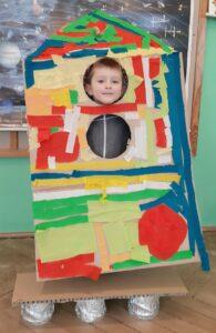Na tle mapy z układem słonecznym widać rakietę, przez górne okrągłe okienko widać twarz dziecka.