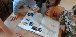 Na stole leży książka o kosmosie, którą oglądają dziewczynki.
