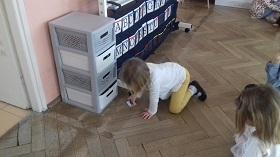 Dziecko klęczy na podłodze w sali, chwyta w ręce mały kwadratowy kartonik ze skrzatem.