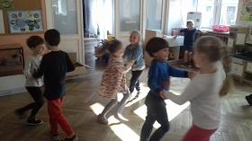 Dzieci trzymające się za ręce i tańczące w parach na podłodze w sali.