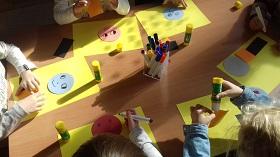 Dzieci siedzące przy stole. Na stole leżą żółte kartki papieru, kleje oraz flamastry.