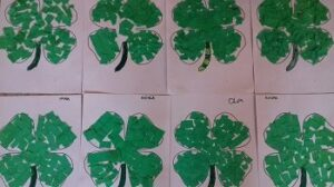 Prace plastyczne dzieci, na których widnieje zielona koniczyna, wyklejona bibułą