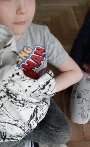 Chłopiec siedzi na podłodze, wkłada rękę do worka.