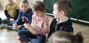 Dzieci siedzą na podłodze, dziewczynka trzyma w ręku krążek drewna i go ogląda.