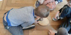 Chłopiec z wykorzystaniem lupy ogląda krążek drewna.