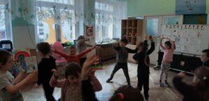 Dzieci stoją w różnych miejscach sali, ręce mają wzniesione w górę.