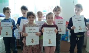 dzieci stoją i trzymają dyplomu