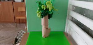 Na zielonej kartce ustawiona jest rolka po papierze toaletowym, w górnej jej części przyklejone są kawałki zielonej krepiny.
