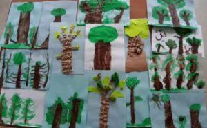Na stole ułożone są prace plastyczne przedstawiające drzewa.