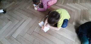 Dziecko rysuje na kartce położonej na podłodze.