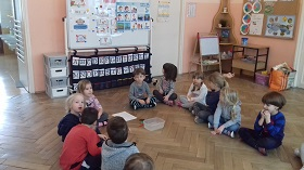 Dzieci siedzące na sali w siadzie skrzyżnym. Część dzieci zwrócona jest twarzą do tablicy. Jedno dziecko podnosi rękę do góry.