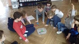 Dzieci siedzące na podłodze w sali, zaglądają do pojemnika. Na środku stoi plastikowy pojemnik z wodą, w którym pływają przedmioty. Dzieci patrzą w stronę pojemnika.
