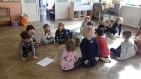 Dzieci siedzące na podłodze w sali, w dwóch rzędach. Część dzieci odwrócona tyłem. Na podłodze leży kartka A4.