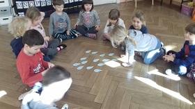 Dzieci siedzące na podłodze w sali, w siadzie skrzyżnym. Na podłodze leżą wycięte z papieru niebieskie kropelki z imionami dzieci. Jedno dziecko patrzy na kropelki.