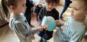 Troje dzieci stoi obok siebie, jedno dziecko trzyma biały balon, a dwoje dzieci po niebieskim kółku.