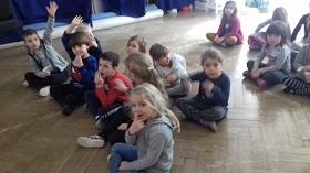 Dzieci siedzące na podłodze w sali, w siadzie skrzyżnym. Dzieci zwrócone twarzą do aparatu. Część dzieci ma podniesioną rękę do góry.