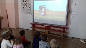 Dzieci siedzące na podłodze w sali, w siadzie skrzyżnym i oglądające film na tablicy interaktywnej. NA tablicy pustynia, na której stoi chłopiec ciemnoskóry i pompuje wodę.