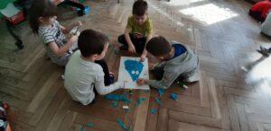 Na podłodze leży kartka z narysowanym kształtem kropli, który dzieci wyklejają kawałkami niebieskich papierów.