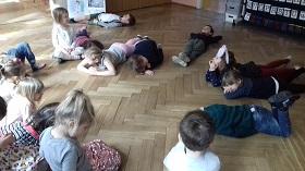 Dzieci leżące i siedzące na podłodze w sali.