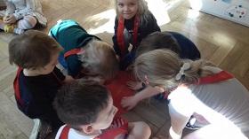 Dzieci mające na sobie czerwone szarfy i kucające przy czerwonym krążku.