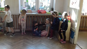 Dzieci stojące na podłodze w sali. Dwójka dzieci siedzi.