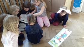 Dzieci siedzące na podłodze w Sali i wpatrujące się w ilustracje na kartkach. Przed nimi leżą dwie kartki z obrazkami.