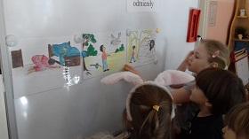 Dzieci stojące przy białej tablicy, zawieszające ilustracje na magnesy. Na tablicy wiszą trzy ilustracje.